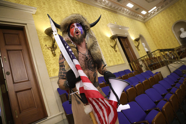 A shirtless man wearing horns and face yells as he stands inside the Capitol while holding the U.S. flag