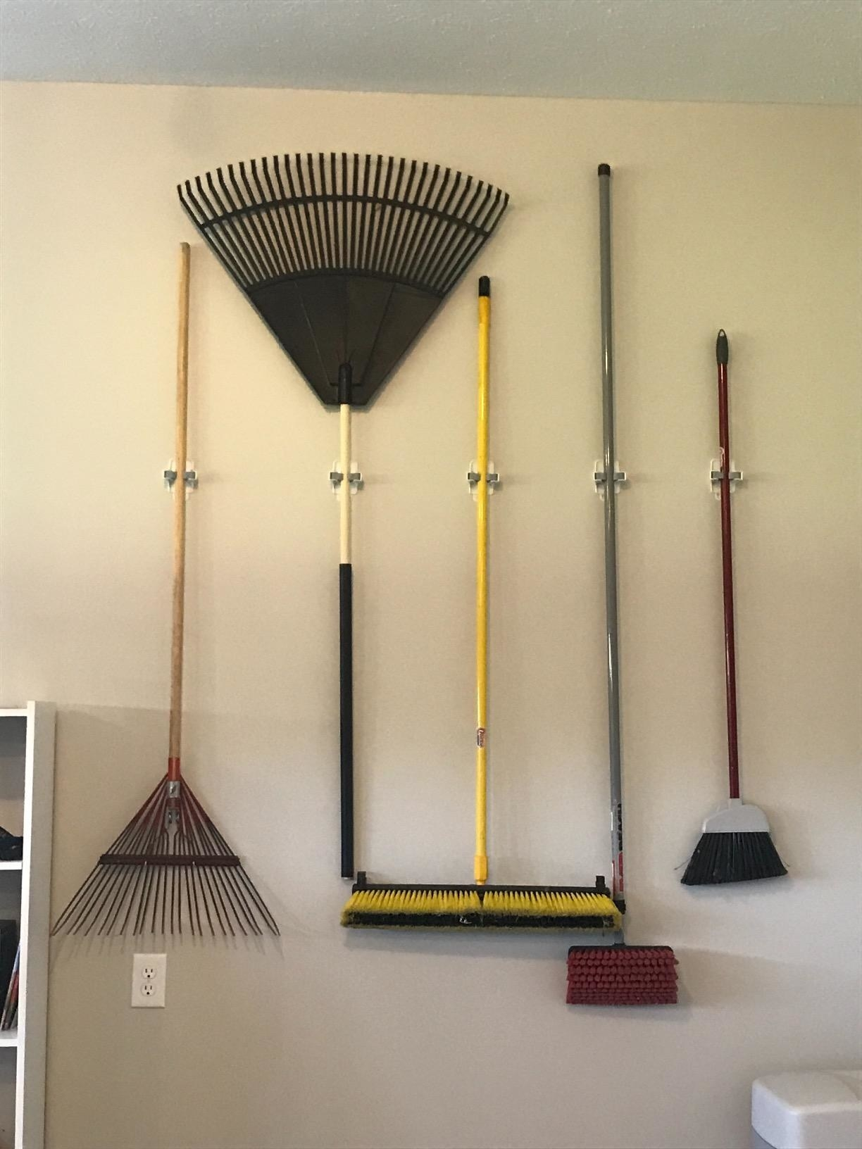 reviewer image of many brooms on wall