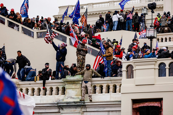 Insurrectionists overrun the steps outside the Capitol while waving US flags and Trump flags