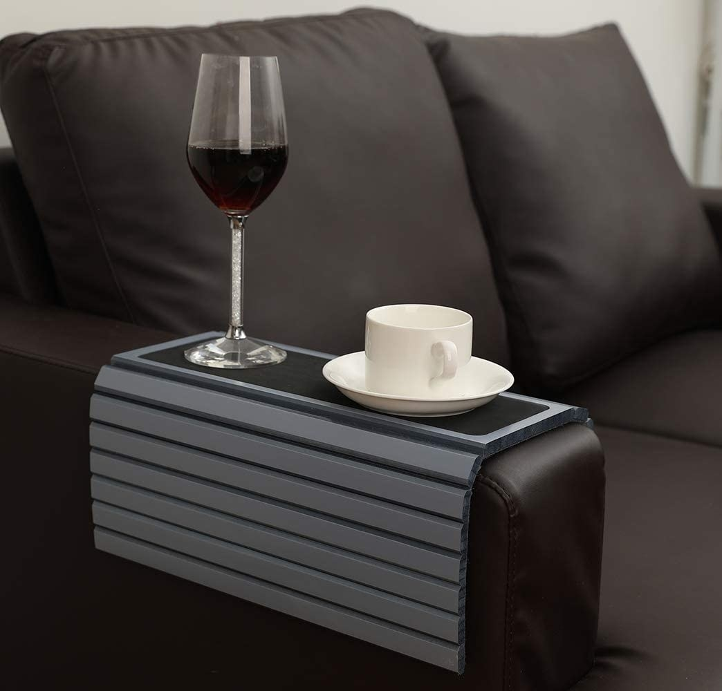 the tray table in grey over the arm of a couch with a coffee cup and wine glass sitting on top of it