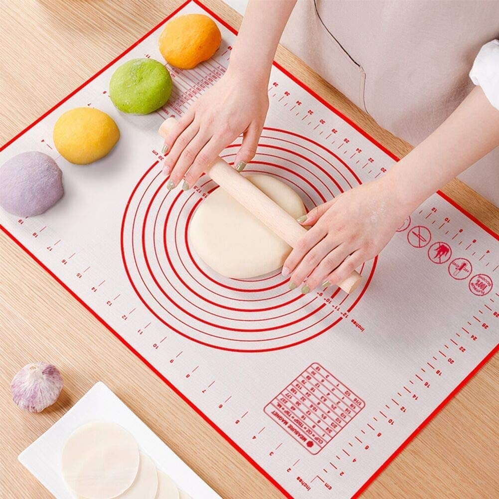 Hands roll out slab of dough on white and red baking mat with measurements
