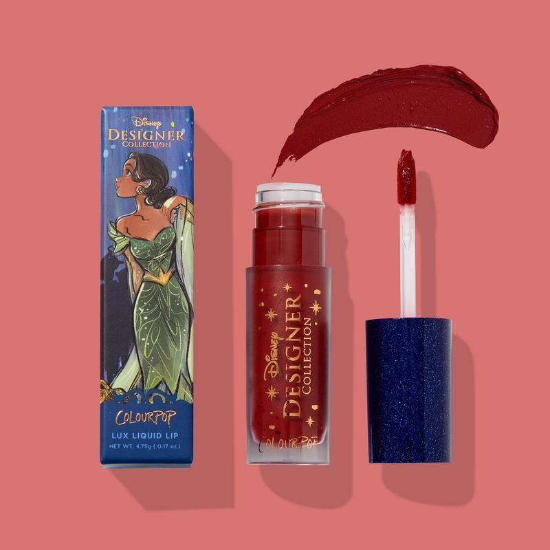 a red lipstick  with a glamorously illustrated tiana on the packaging