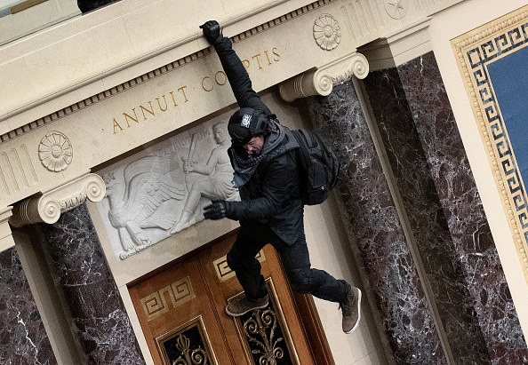 Rioter hangs from a balcony inside the Senate chamber
