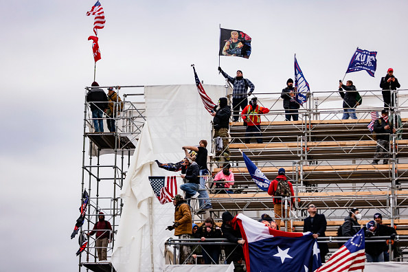 Pro-Trump supporters stand on scaffolding while waving flags