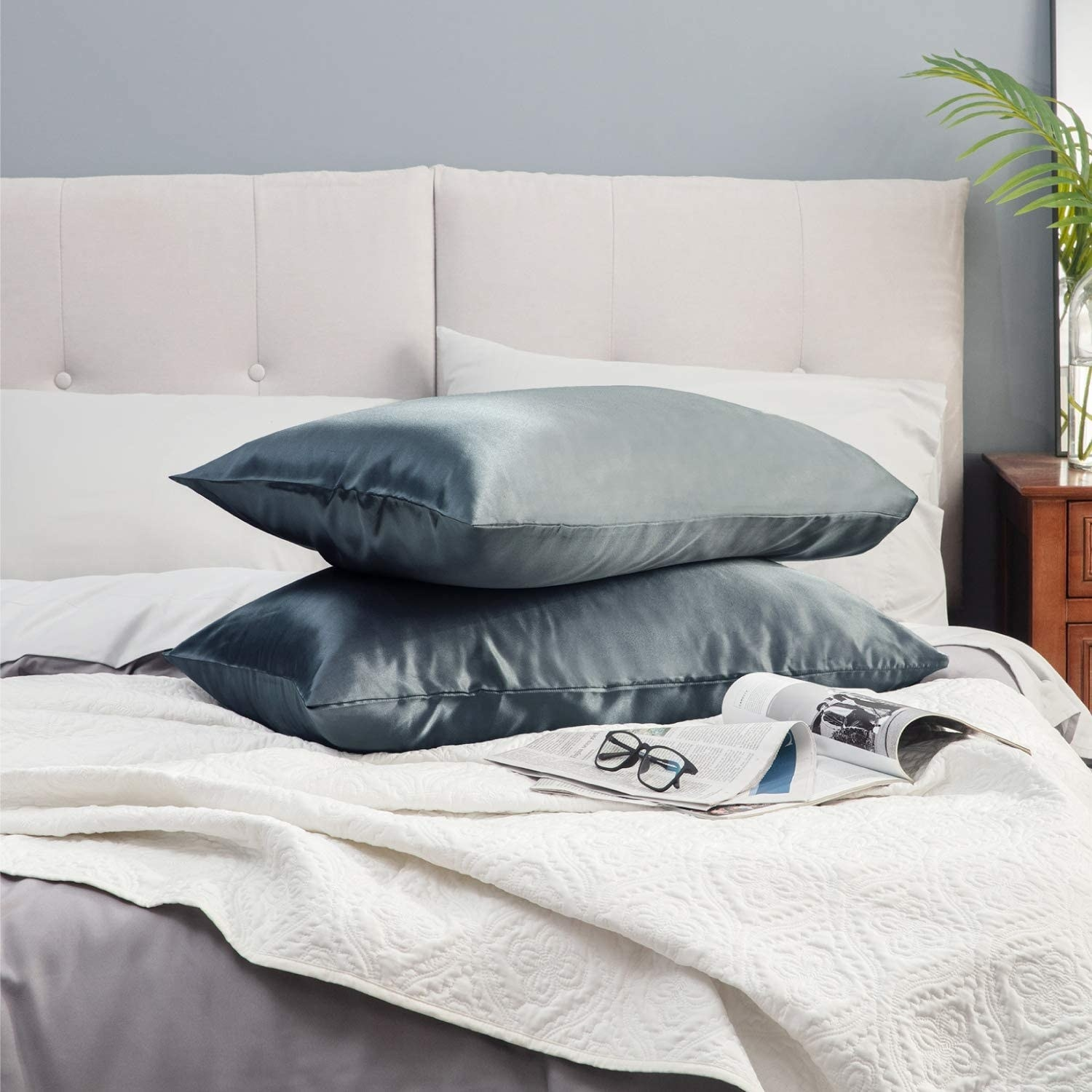 Two pillows with the cases on them stacked on a bed
