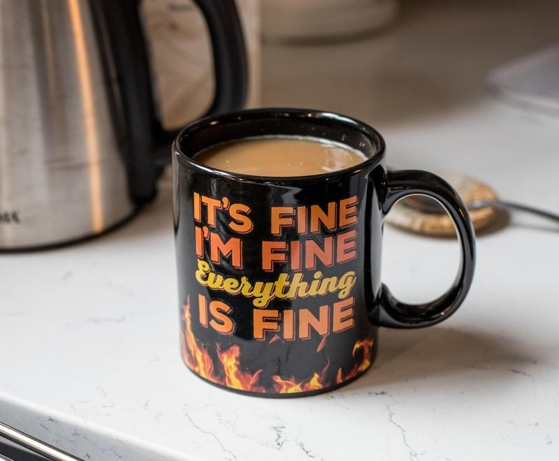 "A black mug with text that says, ""It's fine I'm fine Everything is fine"" surrounded by flames"