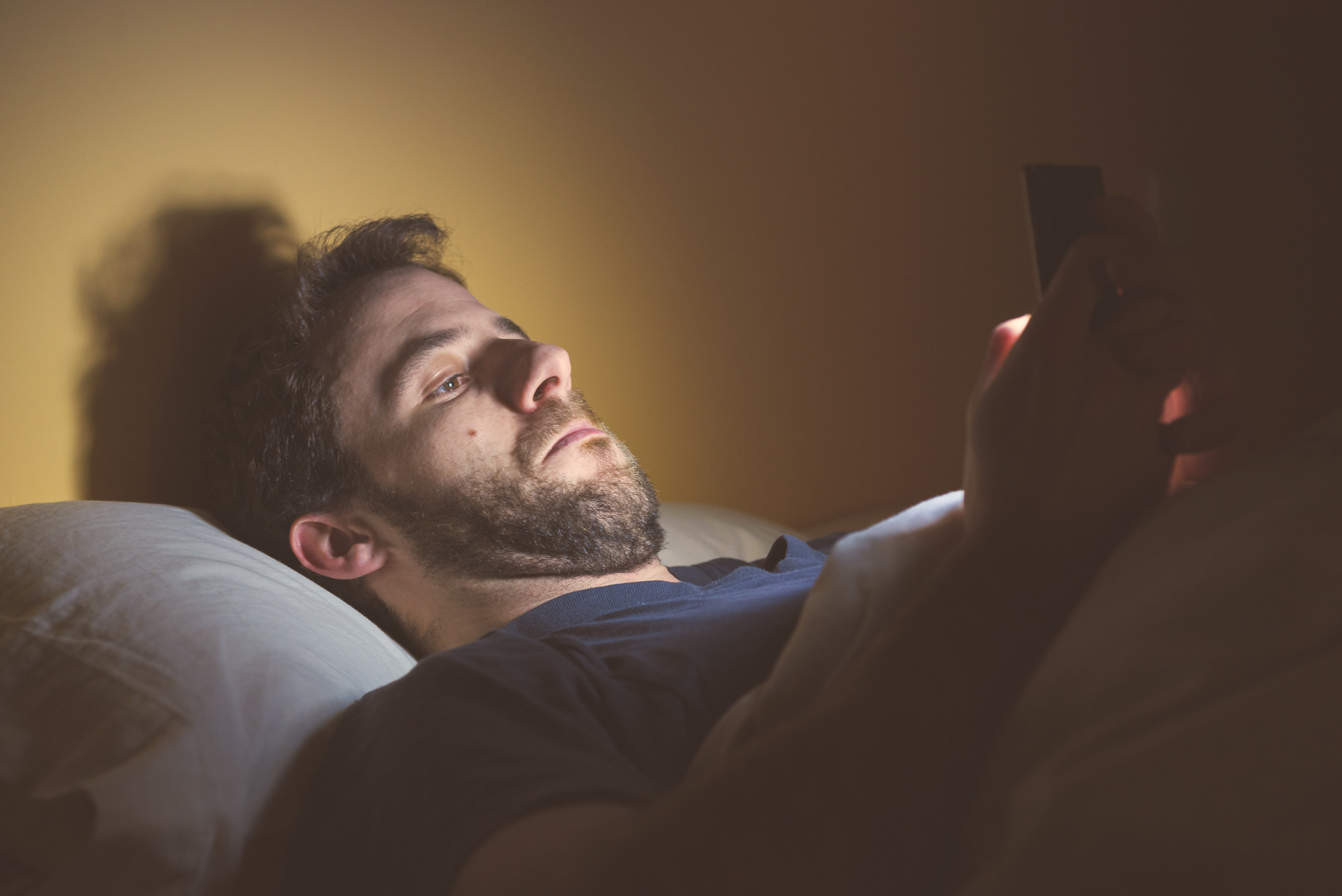 A guy looking at his phone in bed