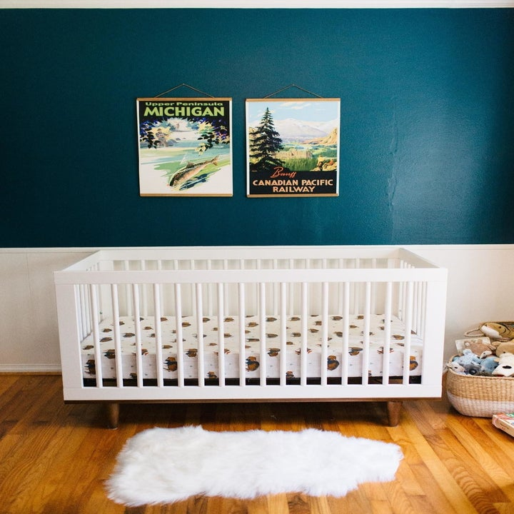 A reviewer's photo of the white, lambskin-shaped area rug in a nursery