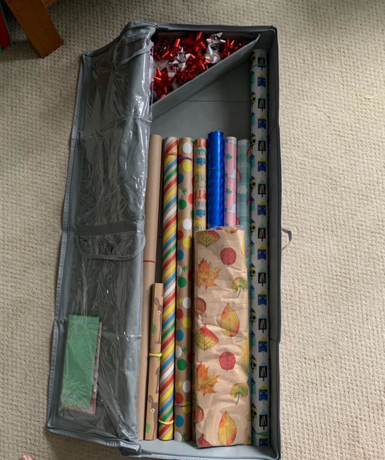 Reviewer's rectangular bag holding eight rolls of wrapping paper with a triangle shelf for bows
