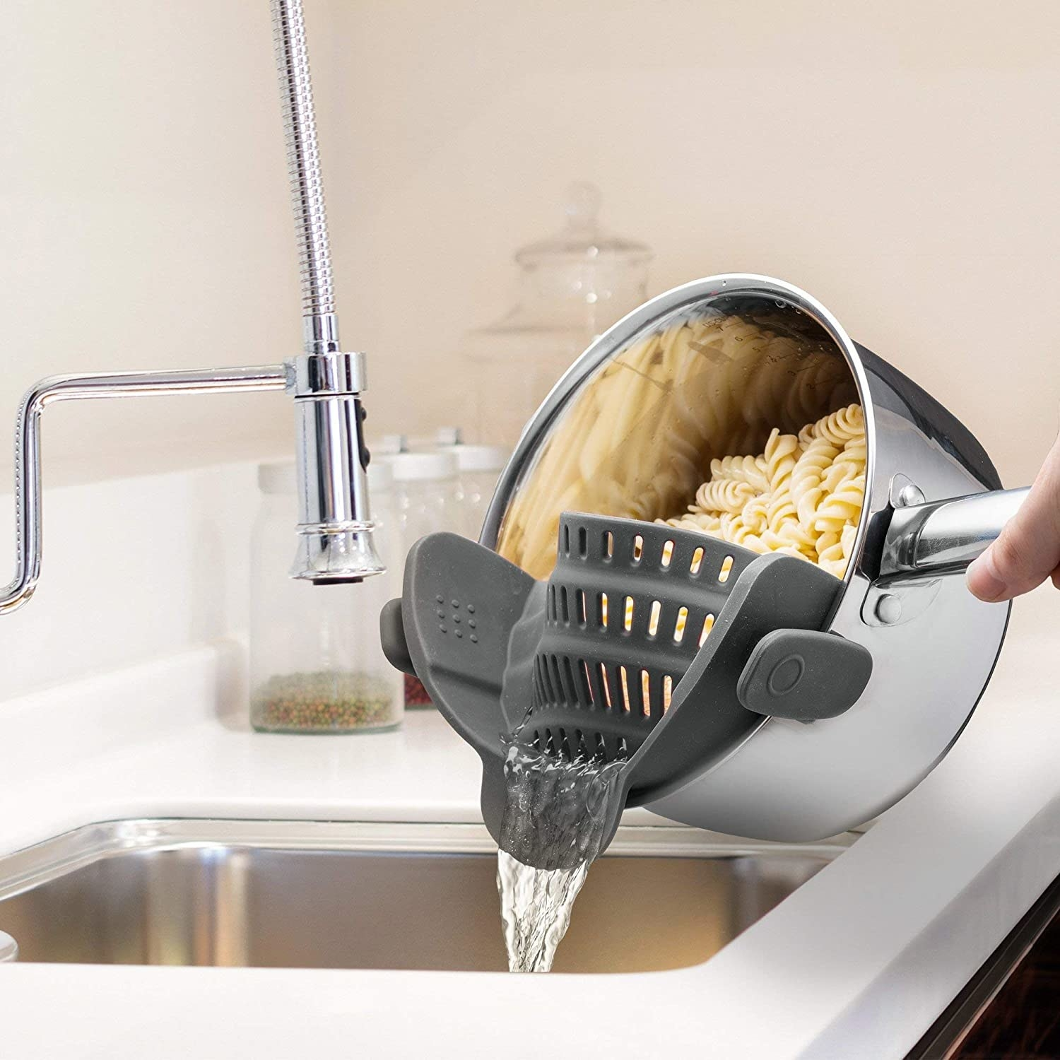 Model uses silver pot with clip-on black strainer to strain water out of a batch of pasta in a sink