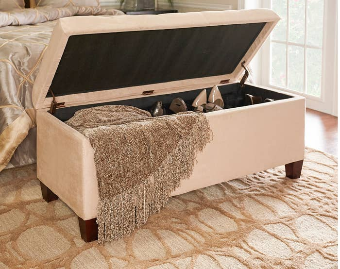 the storage ottoman with a blanket and shoes inside