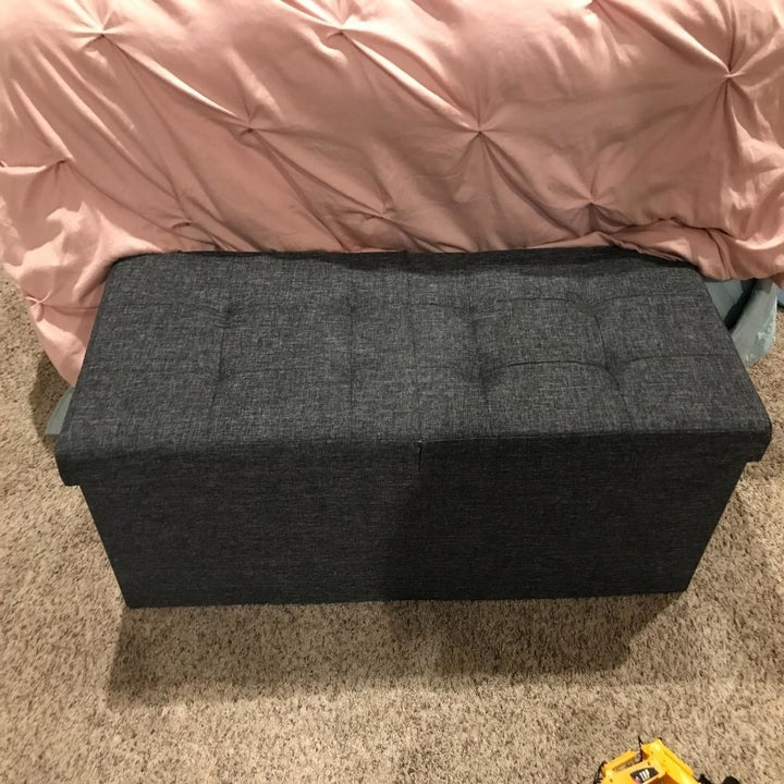reviewer image of the tufted-top ottoman in dark grey in front of a bed