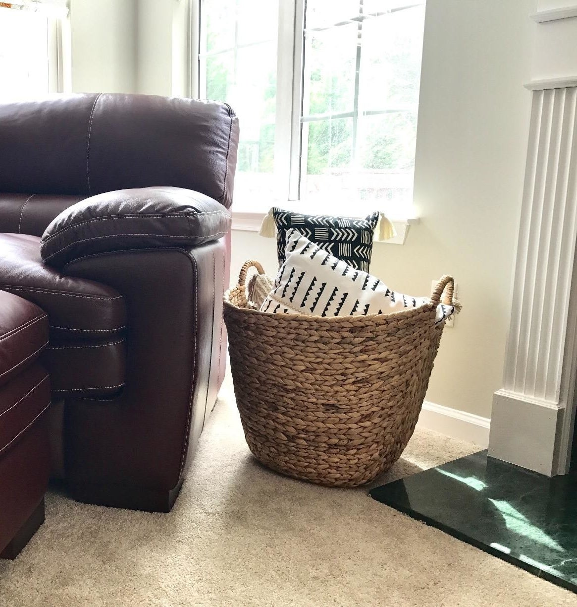 reviewer pic of the woven basket in light tan next to a chair with pillows inside of it