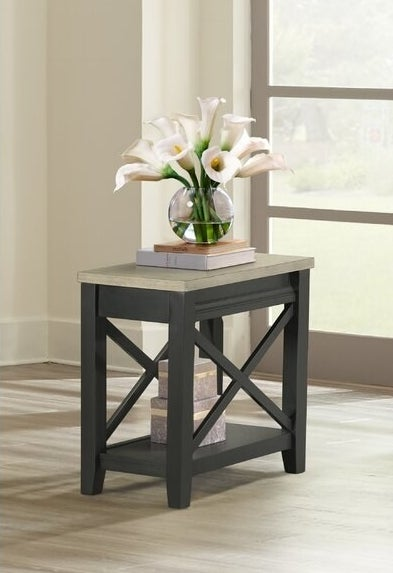 The table, which is dark gray with a light gray top, and X-bracings across the wider side of the legs and a shelf for open storage