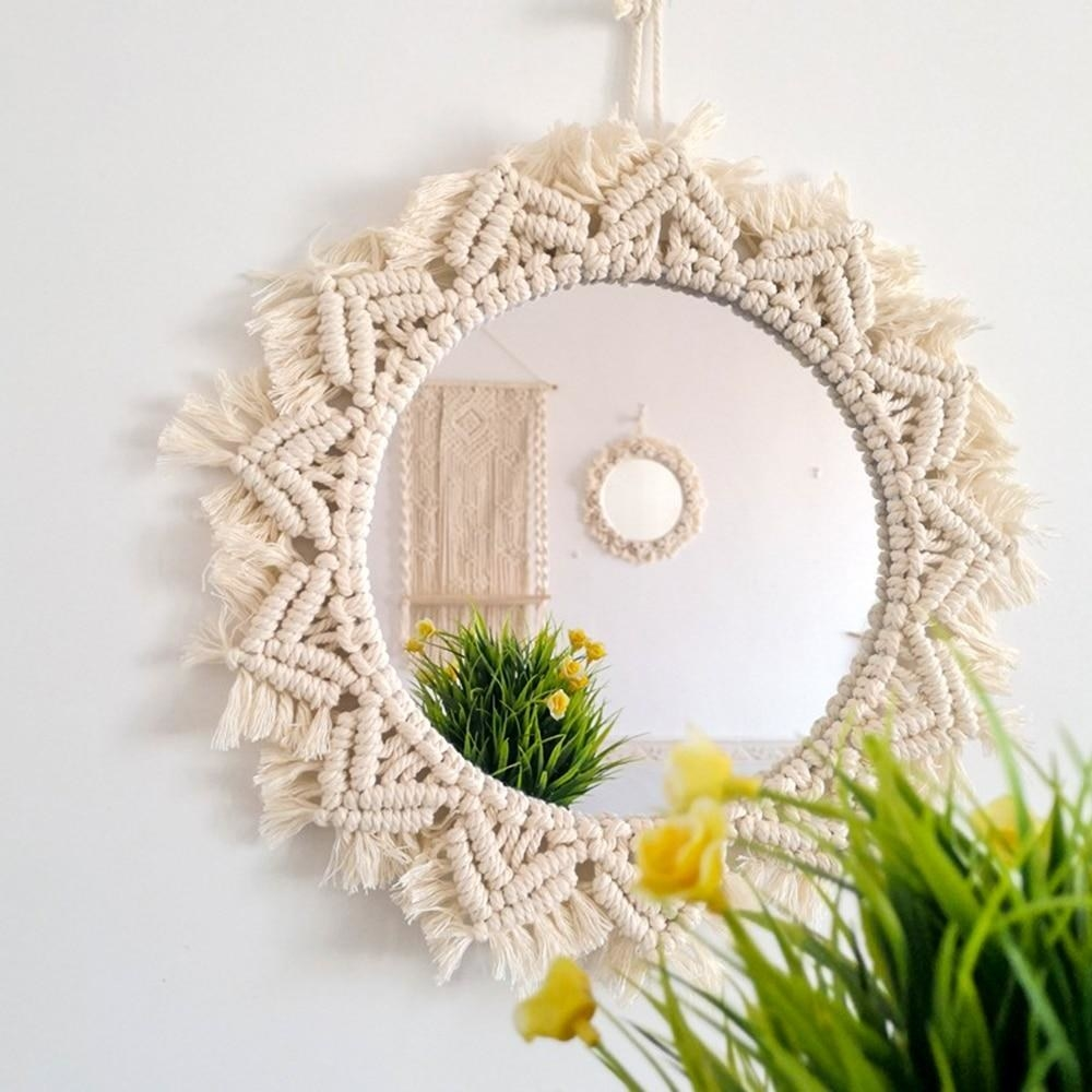 the circular mirror with macrame design around the outside in a v-shaped sun pattern