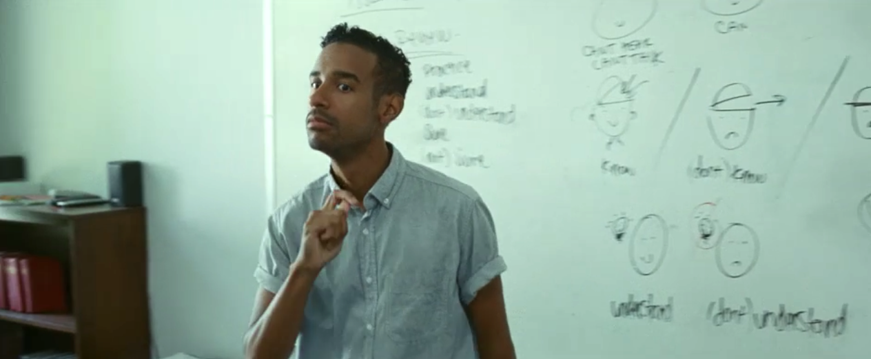 Jeremy Lee Stone as an ASL teacher, signing in front of a white board for a class
