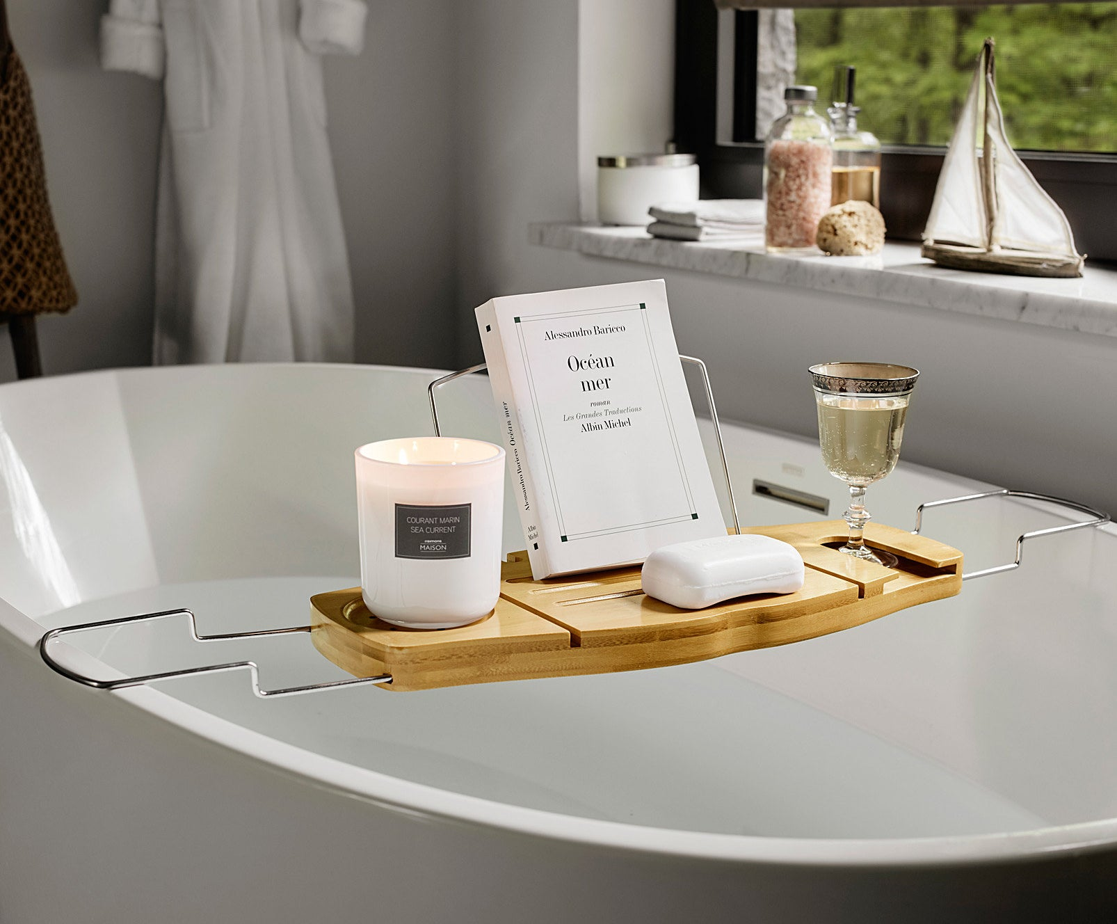 The bathtub tray hovering over a full tub with a candle, book, glasses case, and glass of wine on top