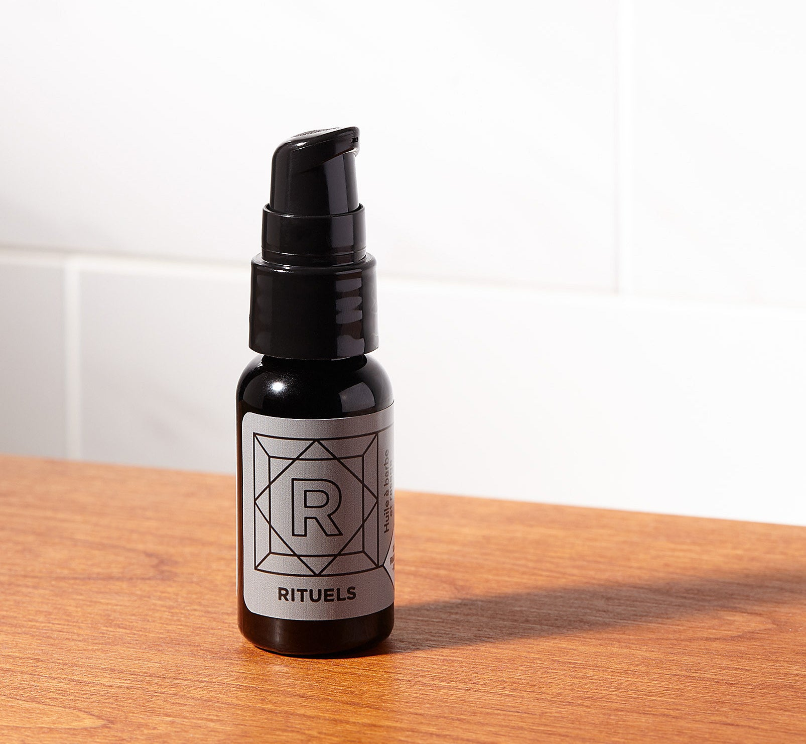 The beard oil in a dark container on a low table