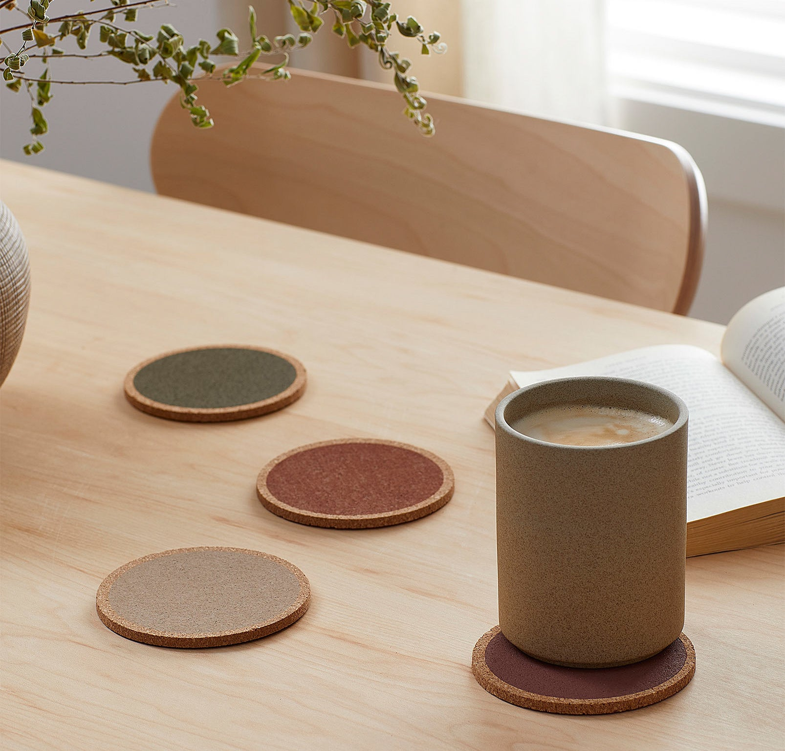 Four coasters on a table, one with a cute mug of coffee sitting on top