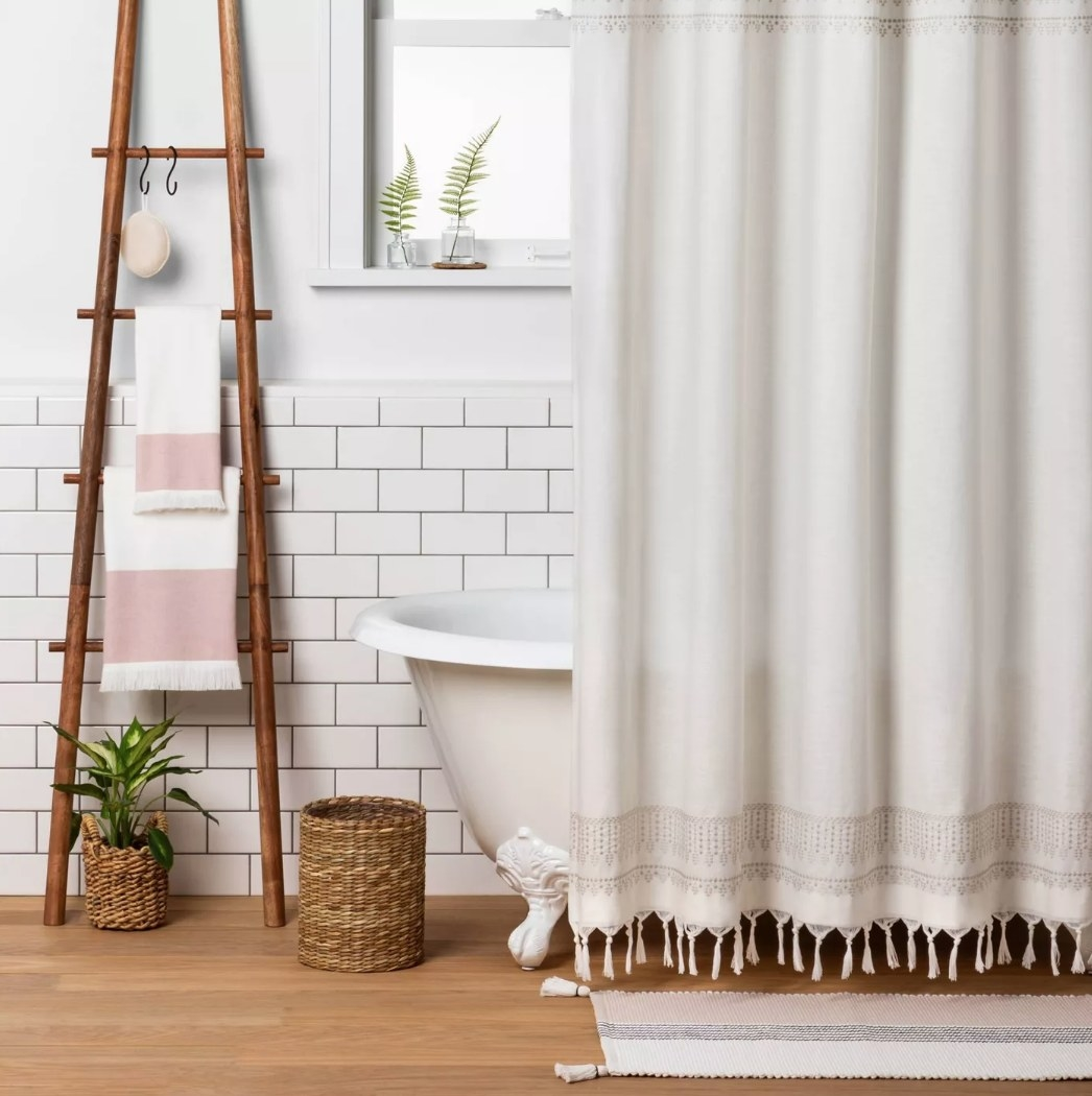 Cream colored shower curtain with tassels in front of white tub