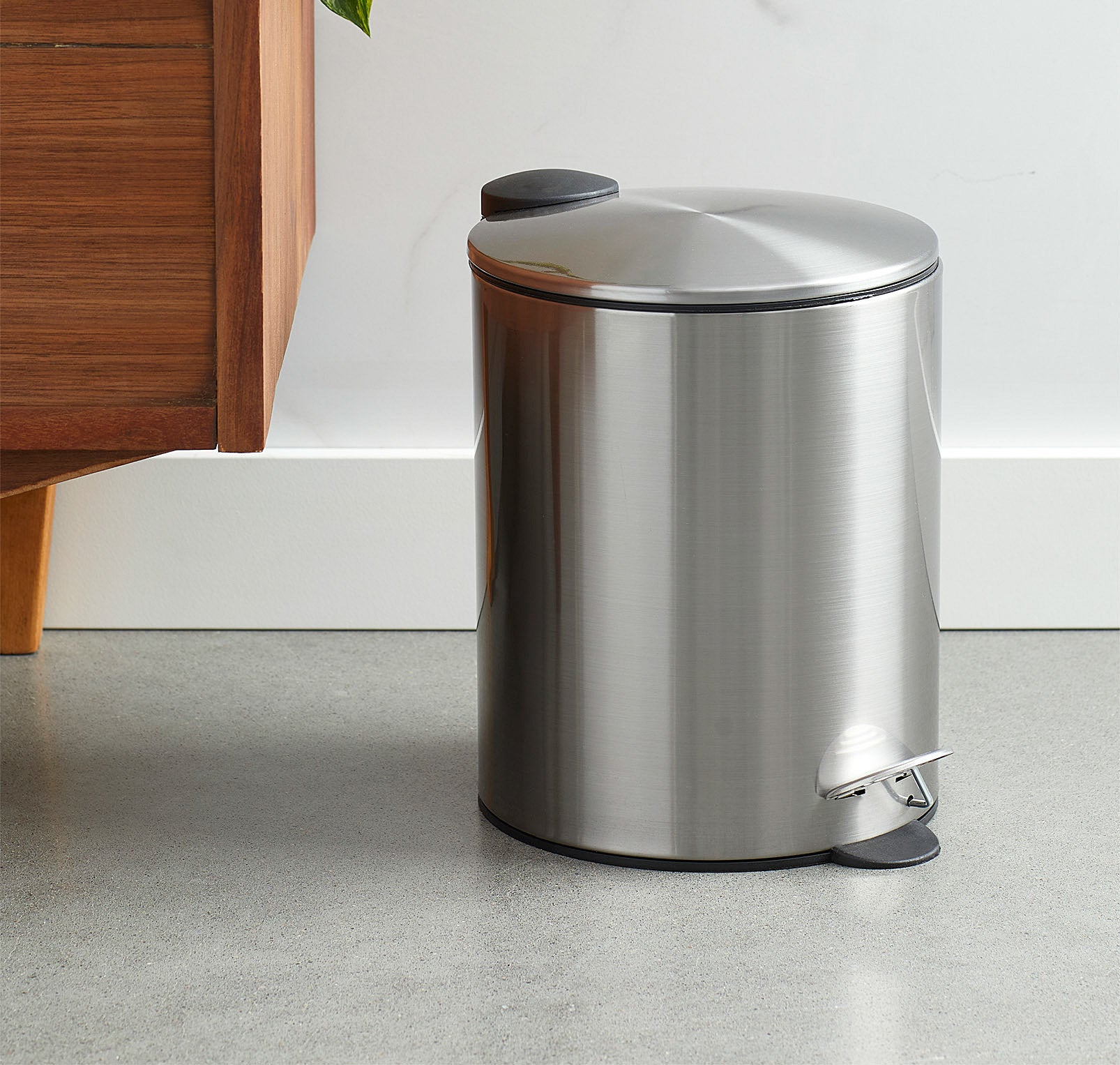 A metallic wastebasket with a pedal opening system next to a wooden dresser