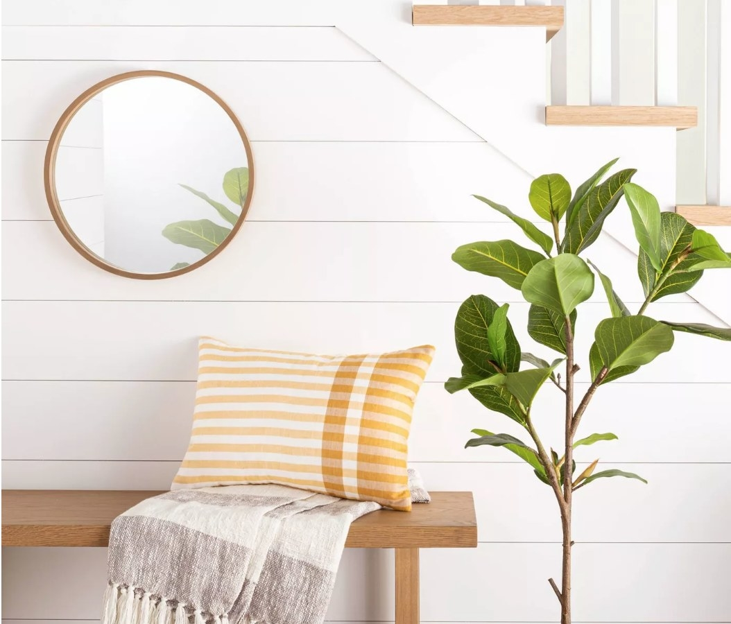 Round wall mirror with wooden border on white wall