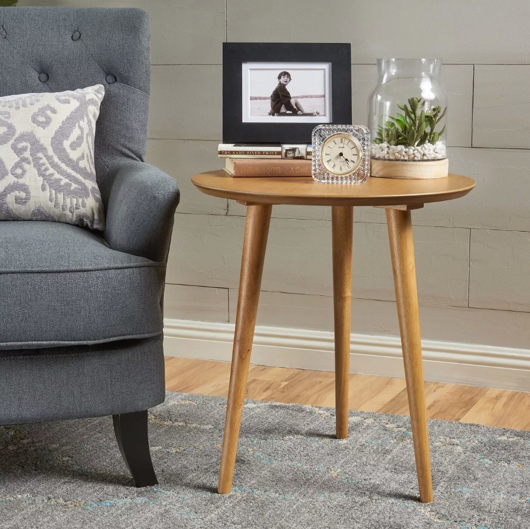 Wooden end table with picture frame, clock and vase on it