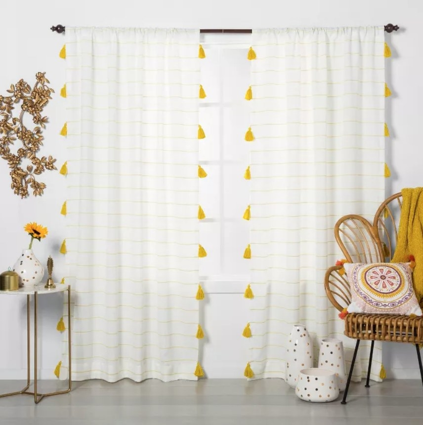 White curtains with yellow pinstripe and yellow tassels