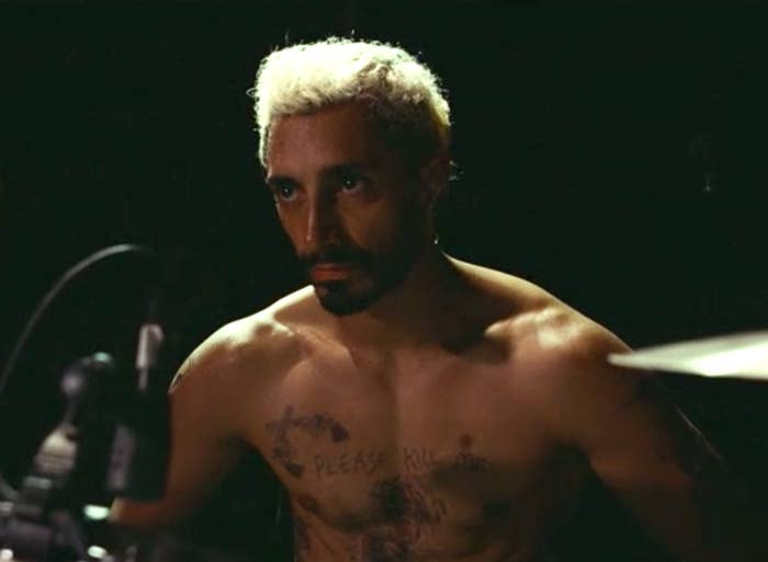 Riz Ahmed as Ruben, shirtless and covered in tattoos, playing drums