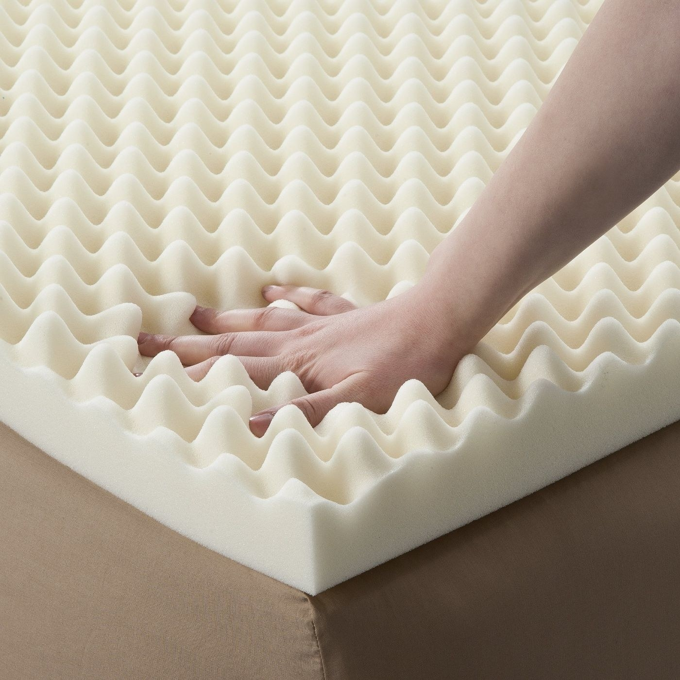 The foam topper, with someone pressing their hand into it to show how soft it is