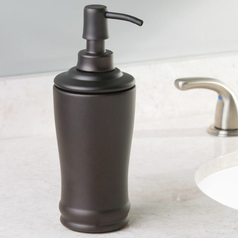 The dispenser, which has a round, cylindrical body of dark metal, and a small pump on the top