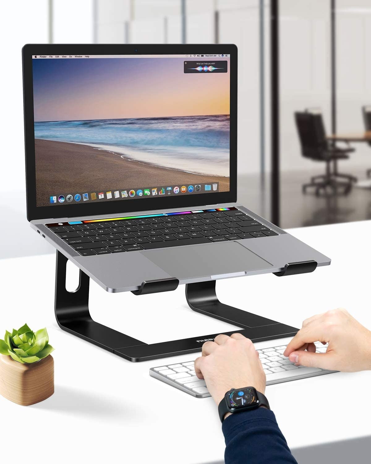 person using a keyboard next to their laptop that's on the stand