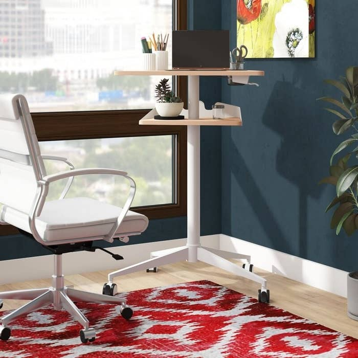 the ebern designs cooperton height adjustable standing desk in the corner of a living space