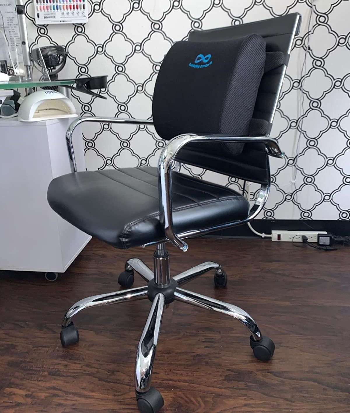 A reviewer photo of a black leather office chair with the lumbar support pillow strapped to the back