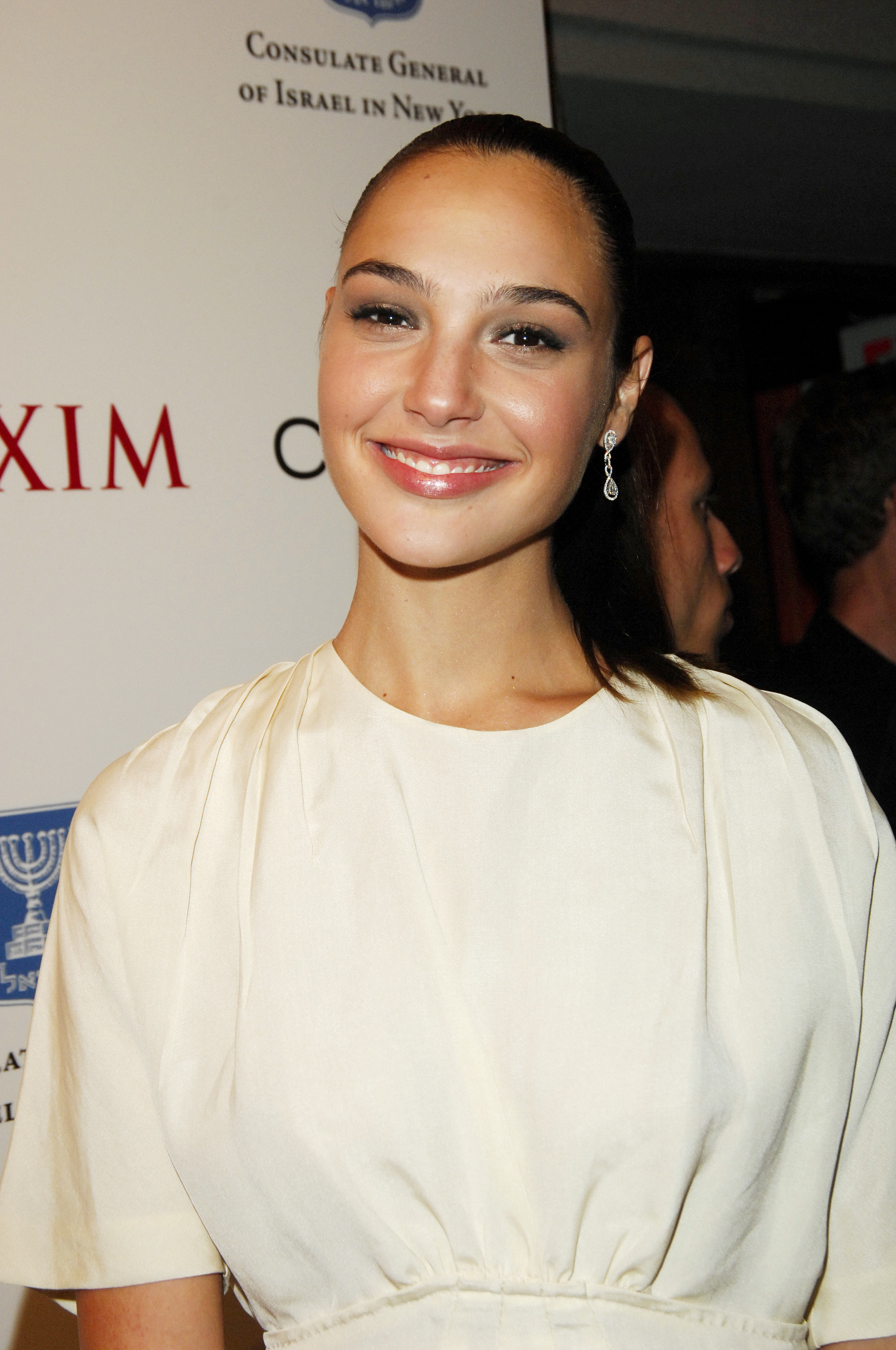 Gal Gadot wearing a white top posing at an event in the early 2000s