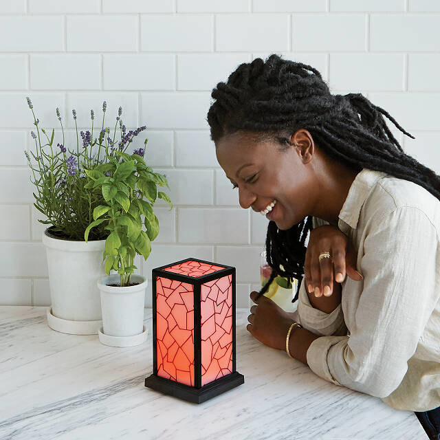 a person glance down at a red long distance friendship lamp