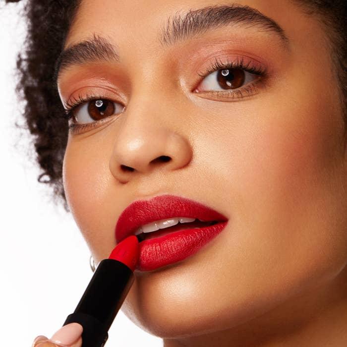 Model applying red lipstick