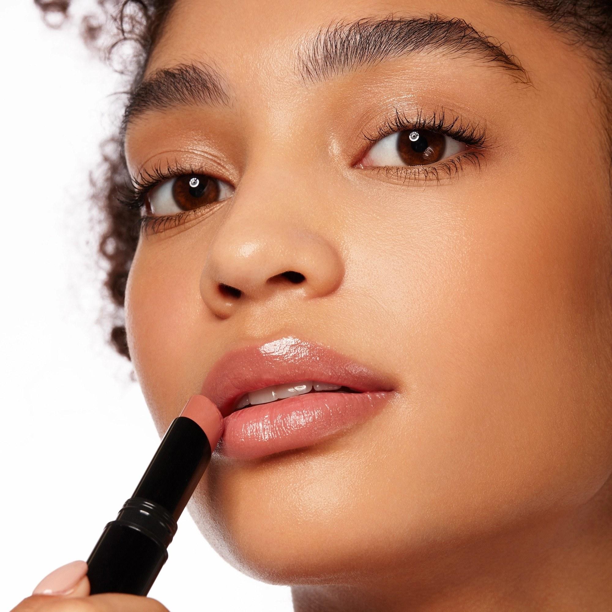Model applying lipstick to lips