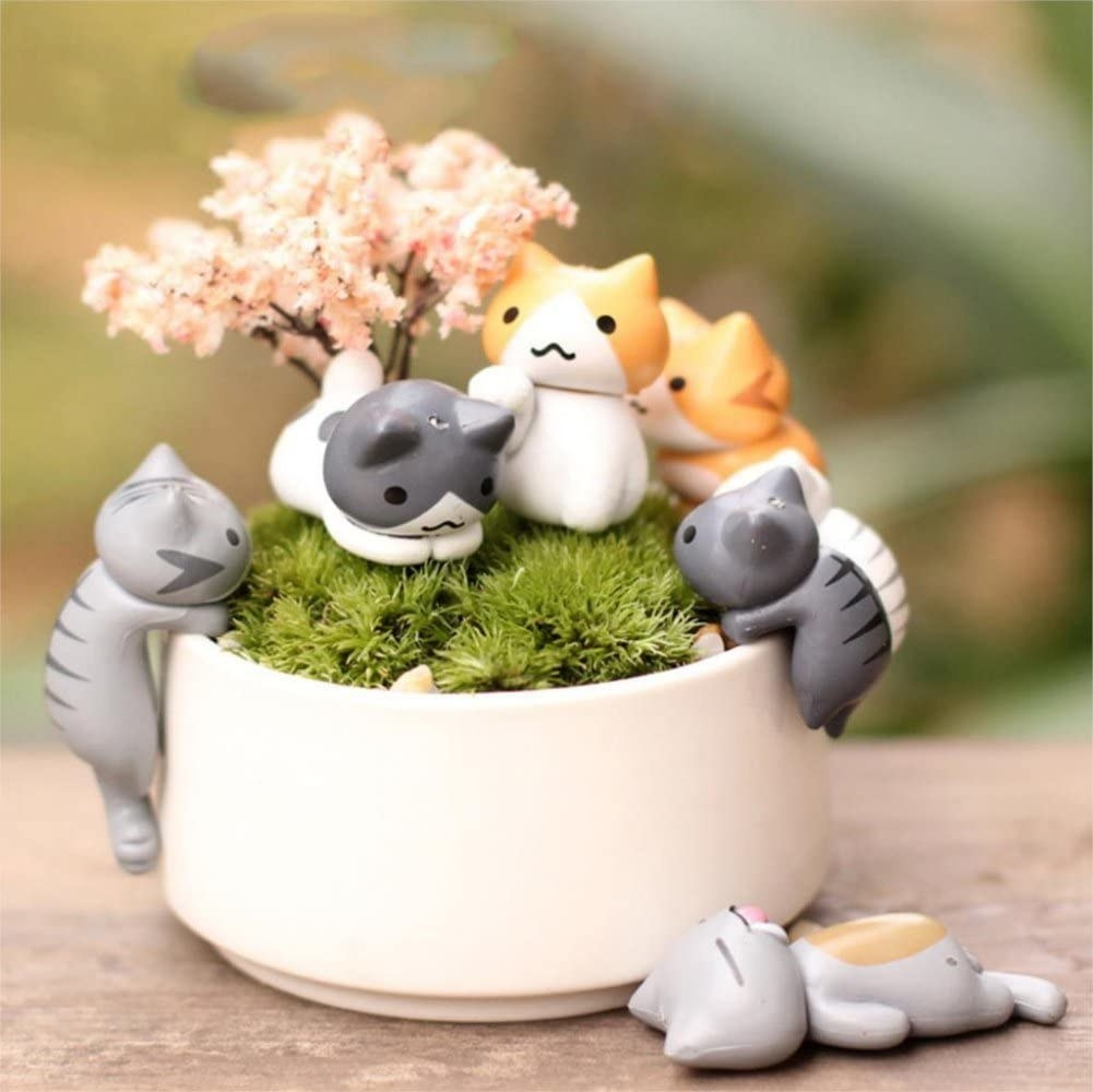 the full set of cat figurines placed on a plotted plant