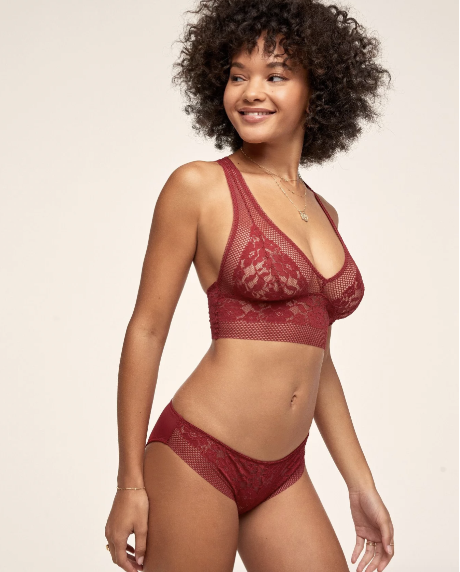 A model in a red lacy bralette and matching underwear