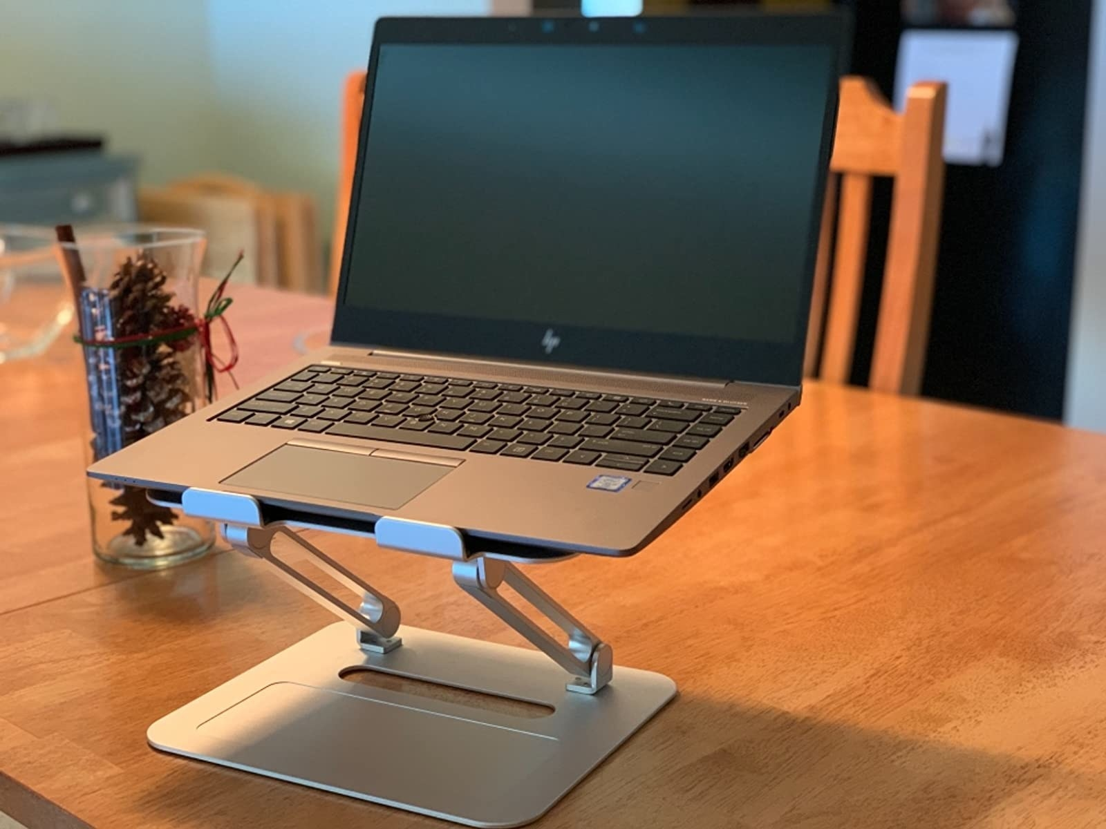 reviewer image of a laptop on top of the TRUNIUM laptop stand which sits on a dining table