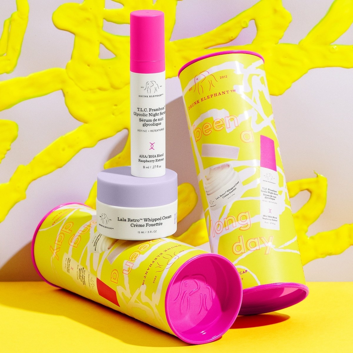 the two products from drunk elephant in mini size next to the yellow and pink tube they are packaged in