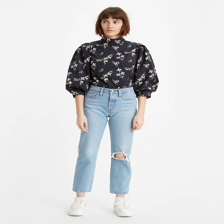 Front view of a model wearing the jeans in tango fray light wash