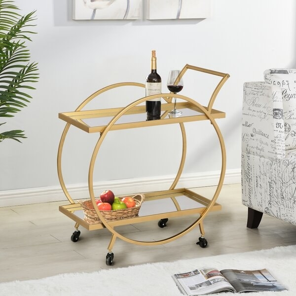 The bar cart, which has two mirrored shelves, four wheels, a gold finish, and a large circular frame on two sides