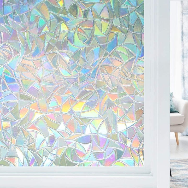 The window cling stuck to a window with light coming through it, emphasizing the array of colors