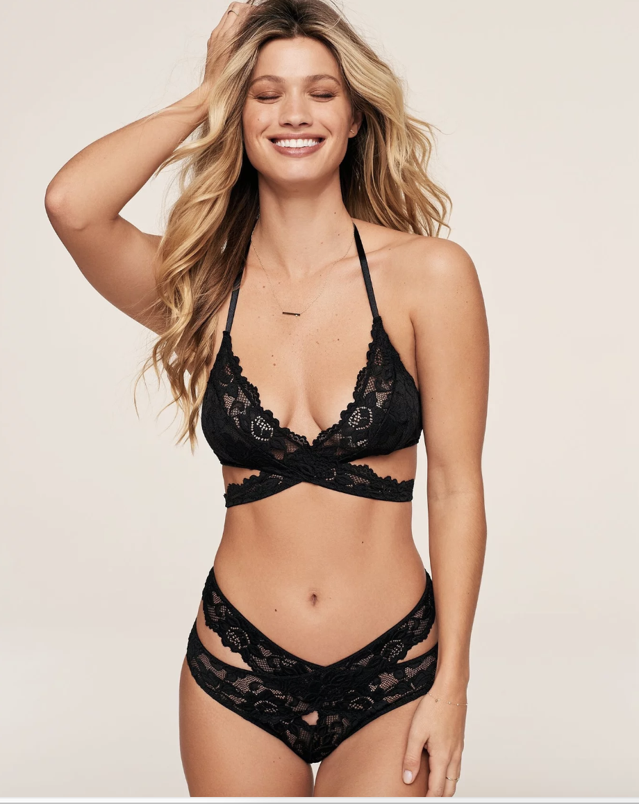 Model in black lacy strapped bra with straps that criss cross on the bottom and matching black underwear