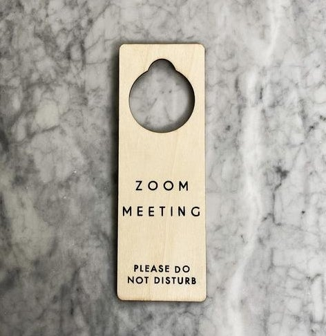 "A natural wood doorknob hanging sign that says ""Zoom Meeting, please do not disturb"" in simple black letters"""