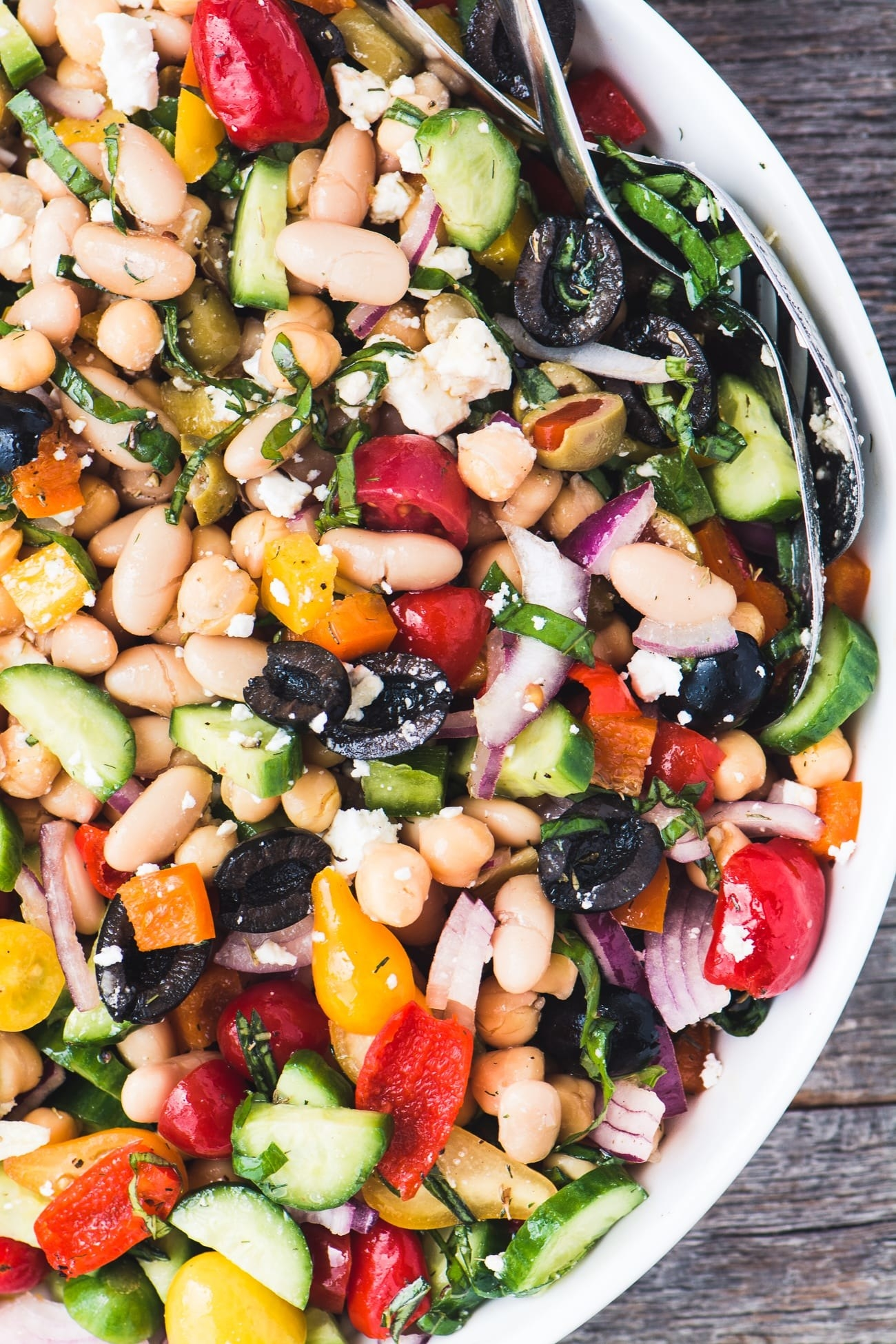 A salad with tomatoes, cucumber, white beans, red onions, and olives.