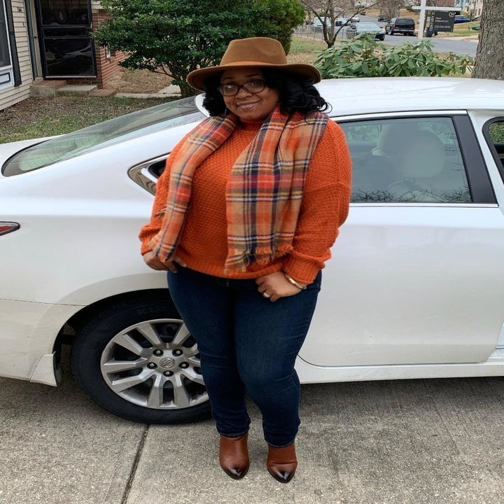 A reviewer wearing the sweater in orange