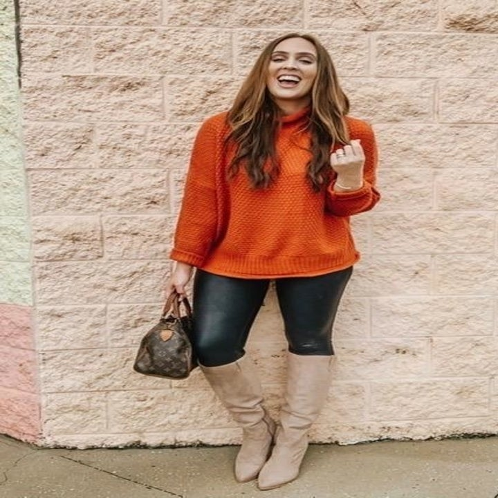A different reviewer wearing the sweater in orange